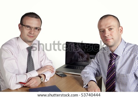 Two businessmen looking at camera with laptop behind - stock photo
