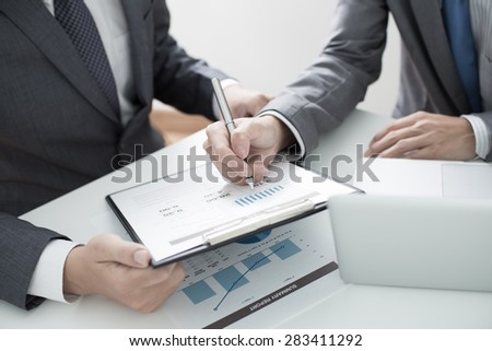 Two businessmen looking at report and having a discussion in office.