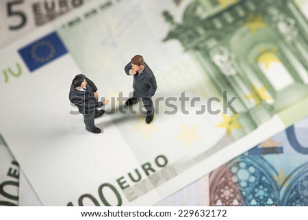 Two businessmen on Euro paper currency - stock photo