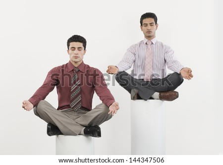 Two businessmen practicing yoga - stock photo