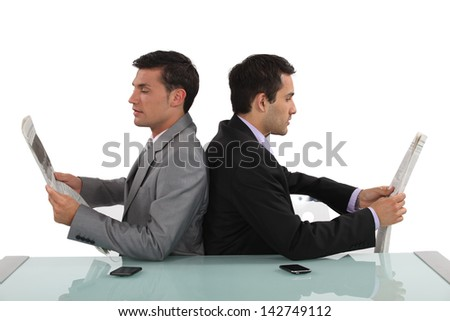 Two businessmen reading newspapers