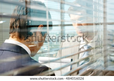 Two businessmen separated by glass wall, one of them reading important document behind blinds