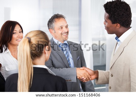 Two Businessmen Shaking Hand In Front Of Colleagues - stock photo