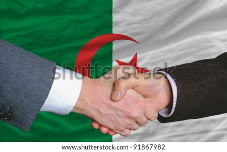 two businessmen shaking hands after good business investment  agreement in algeria, in front of flag - stock photo