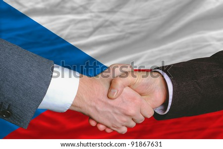 two businessmen shaking hands after good business investment  agreement in czech, in front of flag - stock photo