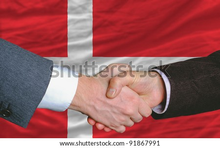 two businessmen shaking hands after good business investment  agreement in denmark, in front of flag - stock photo