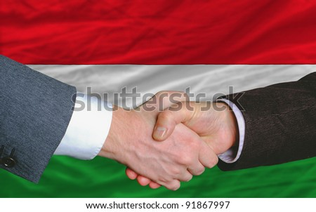 two businessmen shaking hands after good business investment  agreement in hungary, in front of flag - stock photo