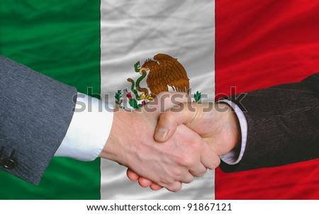 two businessmen shaking hands after good business investment  agreement in mexico, in front of flag - stock photo