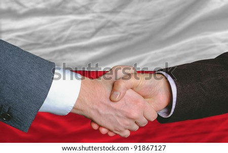 two businessmen shaking hands after good business investment  agreement in portugal, in front of flag - stock photo