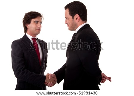 two businessmen shaking hands, and one businessman with his fingers crossed behind his back and smiling, isolated on white background. Studio shot. - stock photo