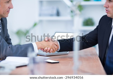 Two businessmen shaking hands and working in the office - stock photo