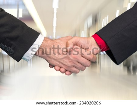 Two businessmen shaking hands in business center - stock photo