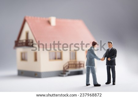 Two businessmen shaking hands in front of a house - stock photo