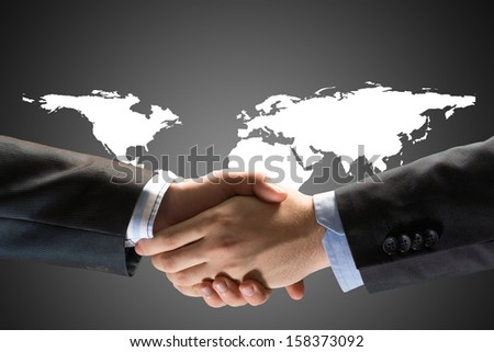 Two businessmen shaking hands on a background map of the world, the concept of success in the business world