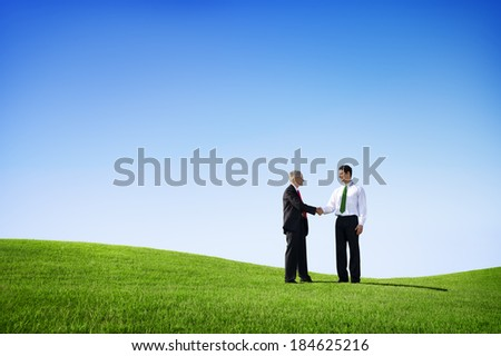 Two Businessmen Shaking Hands On a Green Hill - stock photo