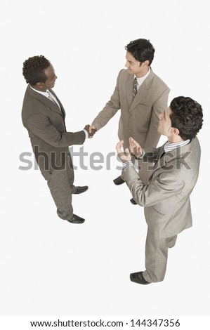 Two businessmen shaking hands with another businessman clapping