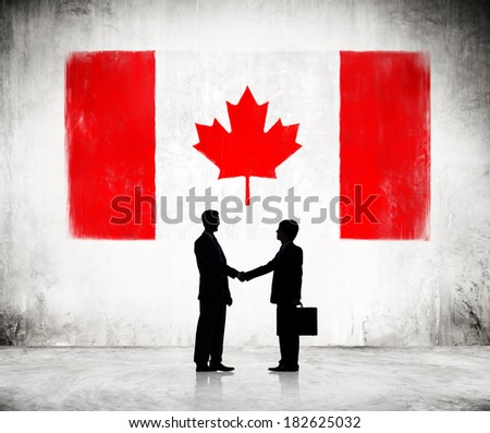 Two Businessmen Shaking Hands With Flag of Canada - stock photo