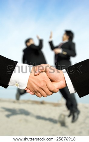 Two businessmen shaking hands with other two businessmen celebrating in the background, can be used for success concept - stock photo
