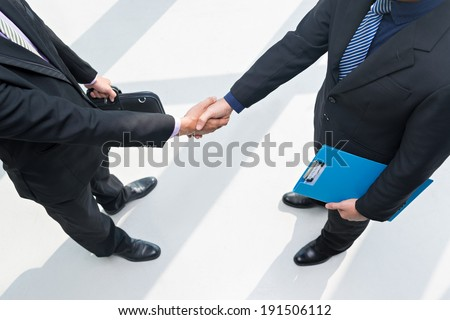 Two businessmen shaking their hands - stock photo