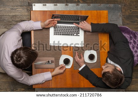 two businessmen sitting in cafe and looking at screen. top view of two colleagues met in restaurant drinking coffee - stock photo