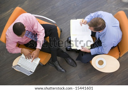 Two businessmen sitting indoors with coffee laptop and folder - stock photo