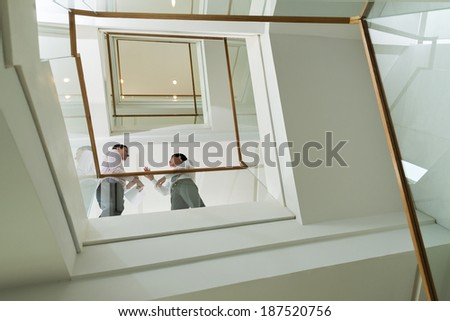 Two businessmen speaking while standing on the staircase - stock photo