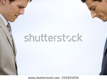Two businessmen standing across from each other, both looking down - stock photo