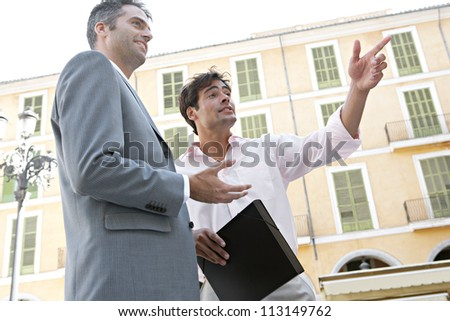 Two businessmen standing and talking near a classic building in a European city. - stock photo