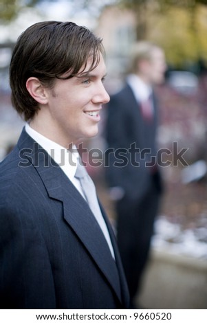 two businessmen standing looking forward in same direction - stock photo