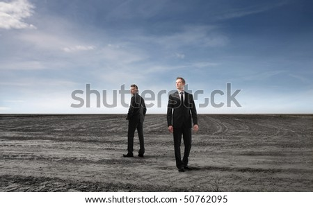 Two businessmen standing on a field - stock photo