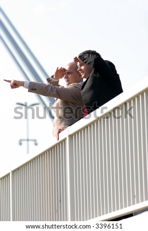 Two businessmen standing on bridge and looking - stock photo