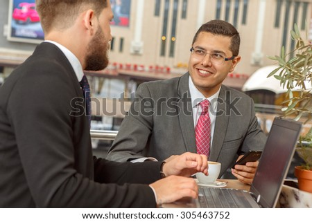 Two businessmen talking in a restaurant and drink coffee