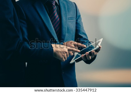 two businessmen using tablet-pc : filtered process - stock photo