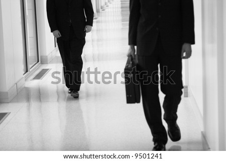 two businessmen walking in hallway