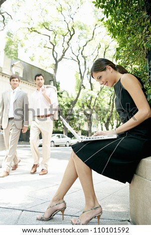 Two businessmen walking in the street and looking at a sexy businesswoman sitting down using her laptop computer. - stock photo