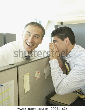 Two businessmen whispering over cubicle wall - stock photo