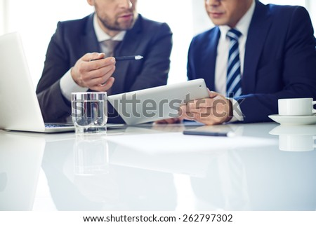 Two businessmen with tablet discussing project - stock photo
