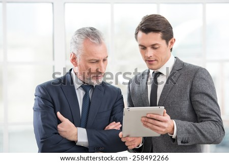 Two businessmen working on tablet computer and discussing something. Office interior with big window - stock photo