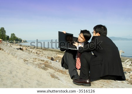 Two businessmen working on their laptop at the beach