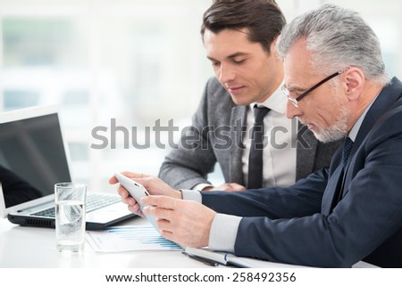 Two businessmen working with documents and tablet computer. Office interior with big window - stock photo