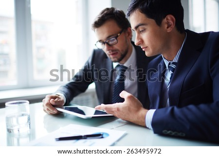 Two businessmen working with touchpad at meeting in office - stock photo