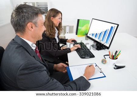 Two Businesspeople Analyzing Graph On Computer In Office - stock photo