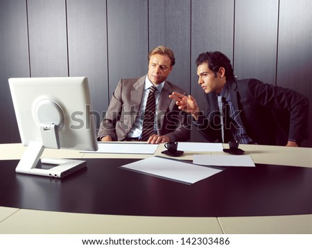 two businesspeople at computer in office - stock photo