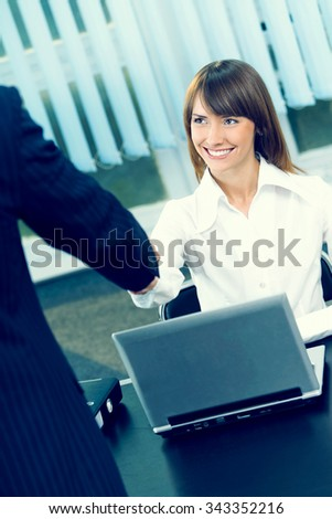 Two businesspeople cheering by handshake at office - stock photo