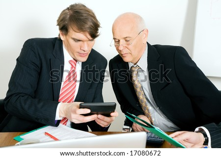 Two businesspeople crunching the numbers - stock photo