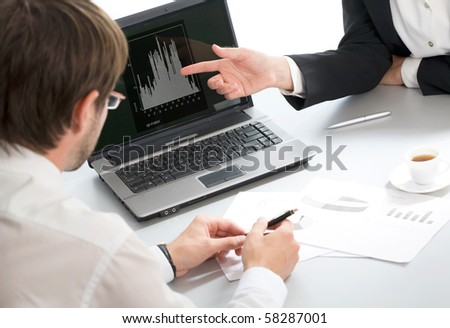 Two businesspeople discussing computer work