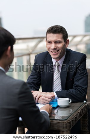 Two businesspeople discussing project, sitting at the table outside - stock photo