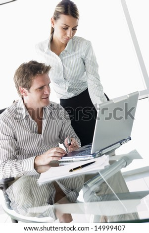 Two businesspeople in boardroom with laptop - stock photo