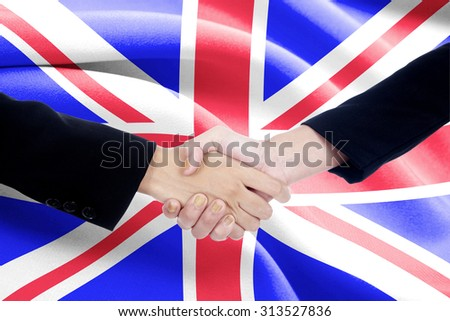 Two businesspeople in business suit, shaking hands in front of united flag background - stock photo