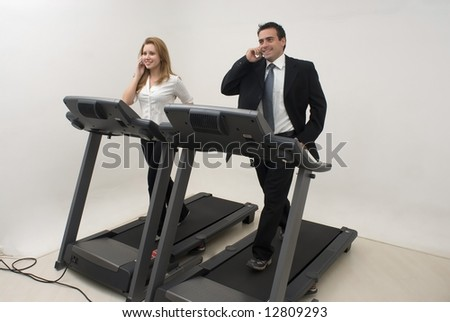 Two businesspeople (male and female) running on a treadmill and talking on their cell phones - stock photo